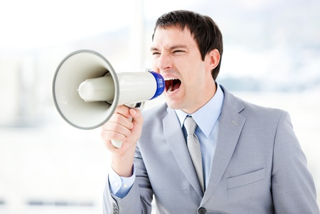 Portrait of an angry businessman using a megaphone  photo