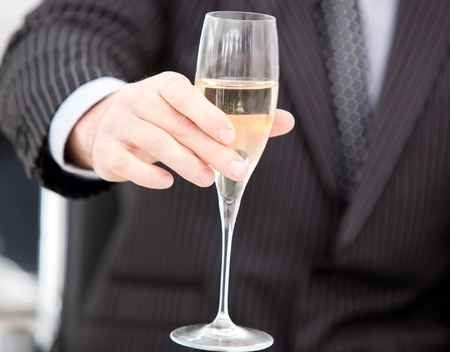 Close-up of a businessman holding a glass of champaign photo
