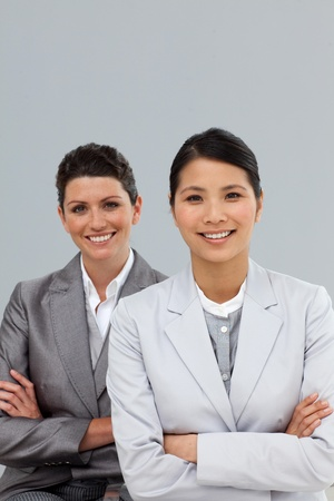 Confident businesswomen with folded arms standing photo