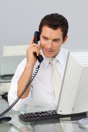 conference call: Attractive businessman on phone and working with a computer Stock Photo