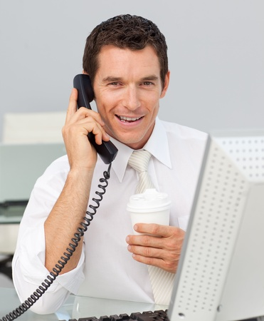 conference call: Smiling businessman on phone drinking a coffee in the office Stock Photo