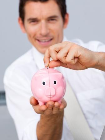 Attractive businessman saving money in a piggybank photo