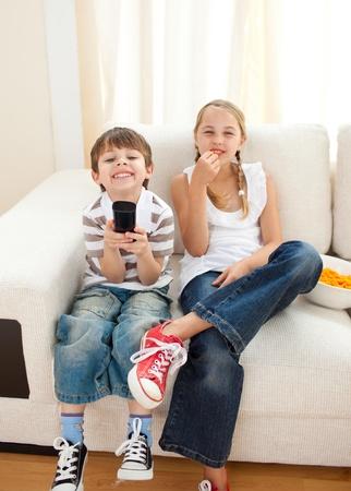 Happy siblings watching TV  photo