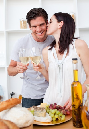 Woman kissing her boyfriend and toasting with white wine photo