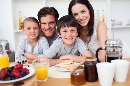 familia comiendo: Sonriente familia desayunando juntos Foto de archivo