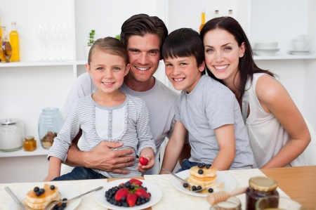 Portrait of parents and children havinf breakfast together photo