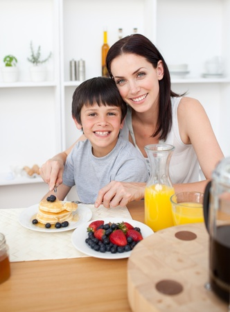 Smiling little boy having breakfast with his mother photo