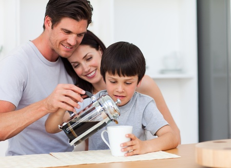 Happy family drinking coffee in the kitchen photo
