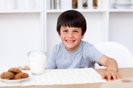 Smiling boy eating biscuits and drinking milk photo