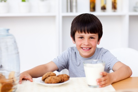 Happy boy eating biscuits and drinking milk photo
