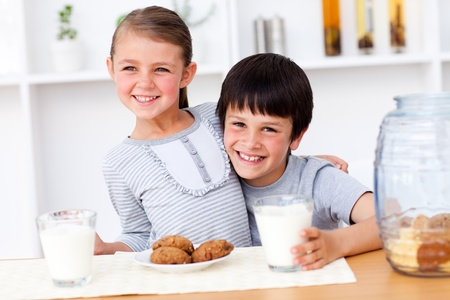 Portrait of  happy brother and sister eating biscuits  photo