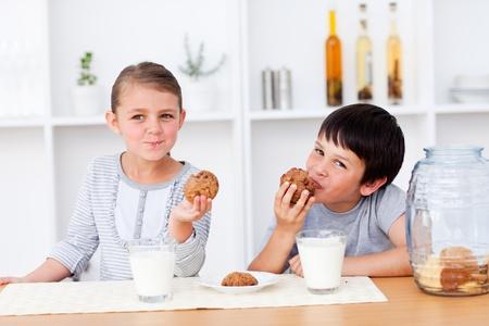 tomando leche: Hermanos comiendo galletas y leche de consumo