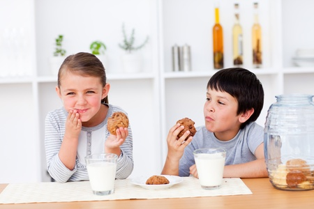 snacking: Happy Siblings eating cookies and drinking milk  Stock Photo