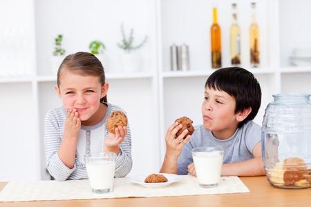 tomando leche: Los hermanos felices comiendo galletas y la leche de consumo Foto de archivo