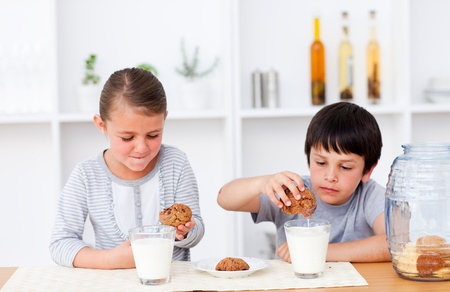Brother and sister eating cookies and drinking milk photo