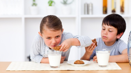 Happy brother and sister eating biscuits and drinking milk  photo
