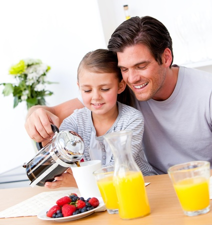 Cheerful father and his daughter having breakfast together Stock Photo - 10110894