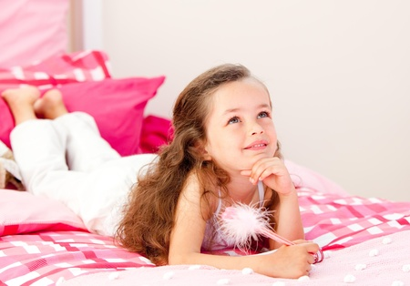 Smiling little girl writing on a notebook lying on her bed photo