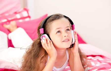 Adorable little girl listening music lying on her bed photo