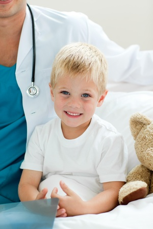 doctor examining woman: Portrait of a smiling little boy sitting on a hospital bed