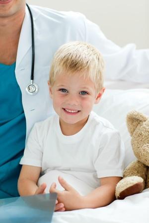 ni�os enfermos: Retrato de un ni�o sonriente, sentado en una cama de hospital
