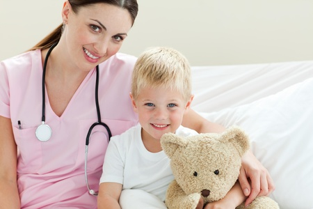 Smiling little boy holding a teddy bear on a hospital bed photo