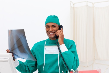 Confident surgeon on phone examining an x-ray photo