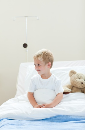 Smiling little boy on a hospital bed photo