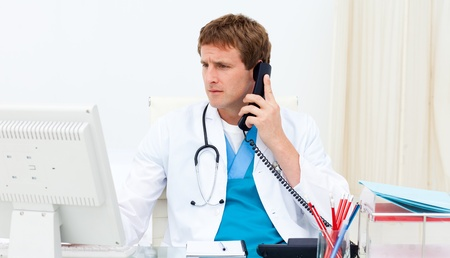 family doctor: Confident doctor on phone at his computer Stock Photo