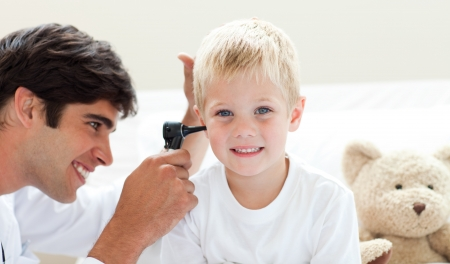 Attractive doctor checking his patients ears  photo