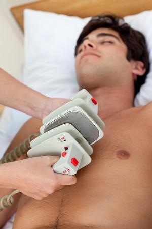 Emergency scene: doctor using a defibrillator Stock Photo - 10096441