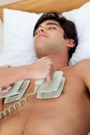 defibrillator: A doctor performimg a CPR with a defibrillator Stock Photo