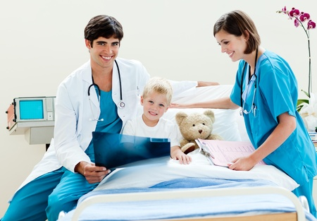 Little boy looking at an x-ray with his doctor and nurse Stock Photo - 10093937