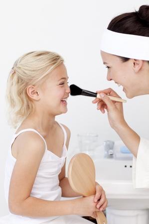 Daughter and mother putting makeup photo