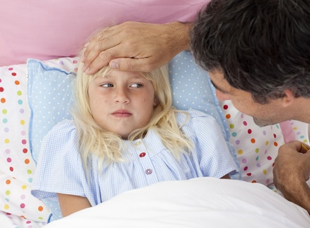 Father taking his daughters temperature with a thermometer photo