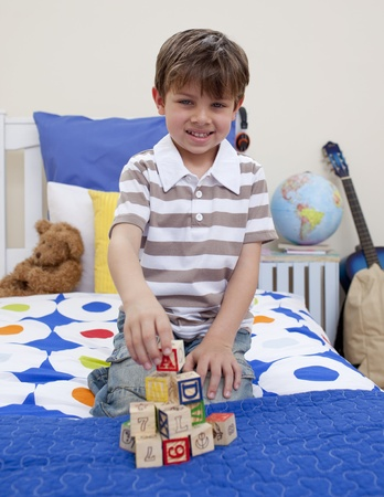 Little boy playing with alphabet cubes photo