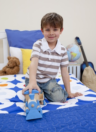 Little boy playing with a train in his bedroom photo