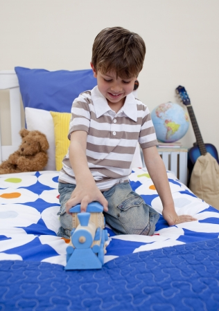 kids room: Happy boy playing with a train in his bedroom