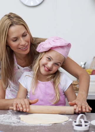 Happy mother and daughter baking in the kitchen photo