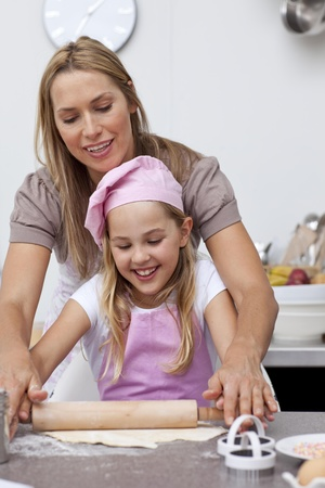 Mother and daughter baking cookies in the kitchen photo