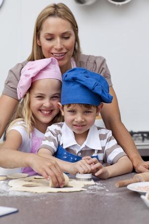 Mother helping her children baking  photo