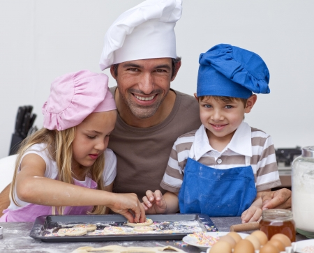 Father and daughter and son baking in the kitchen photo