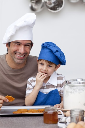 Father and son eating home-made cookies photo