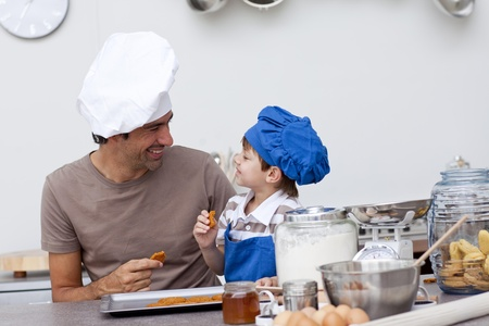 dads: Smiling father and son eating home-made cookies