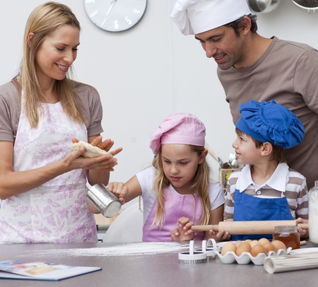 helping children: Mother and father helping children baking in the kitchen Stock Photo