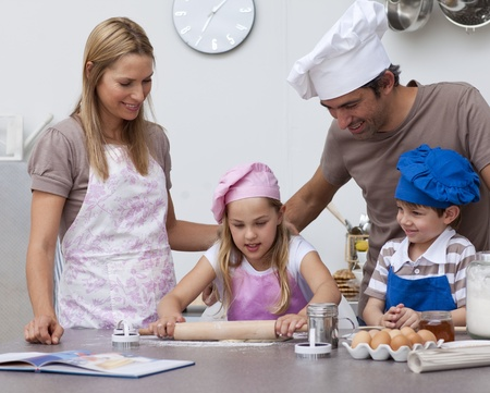 Parents helping children baking in the kitchen photo