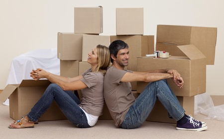 Happy couple sitting on floor unpacking boxes photo