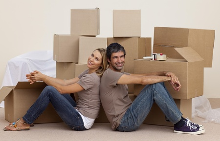 Smiling couple sitting on floor around boxes photo