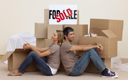 Happy couple sitting on floor after buying house photo