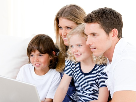 girl notebook: Smiling family surfing on internet Stock Photo